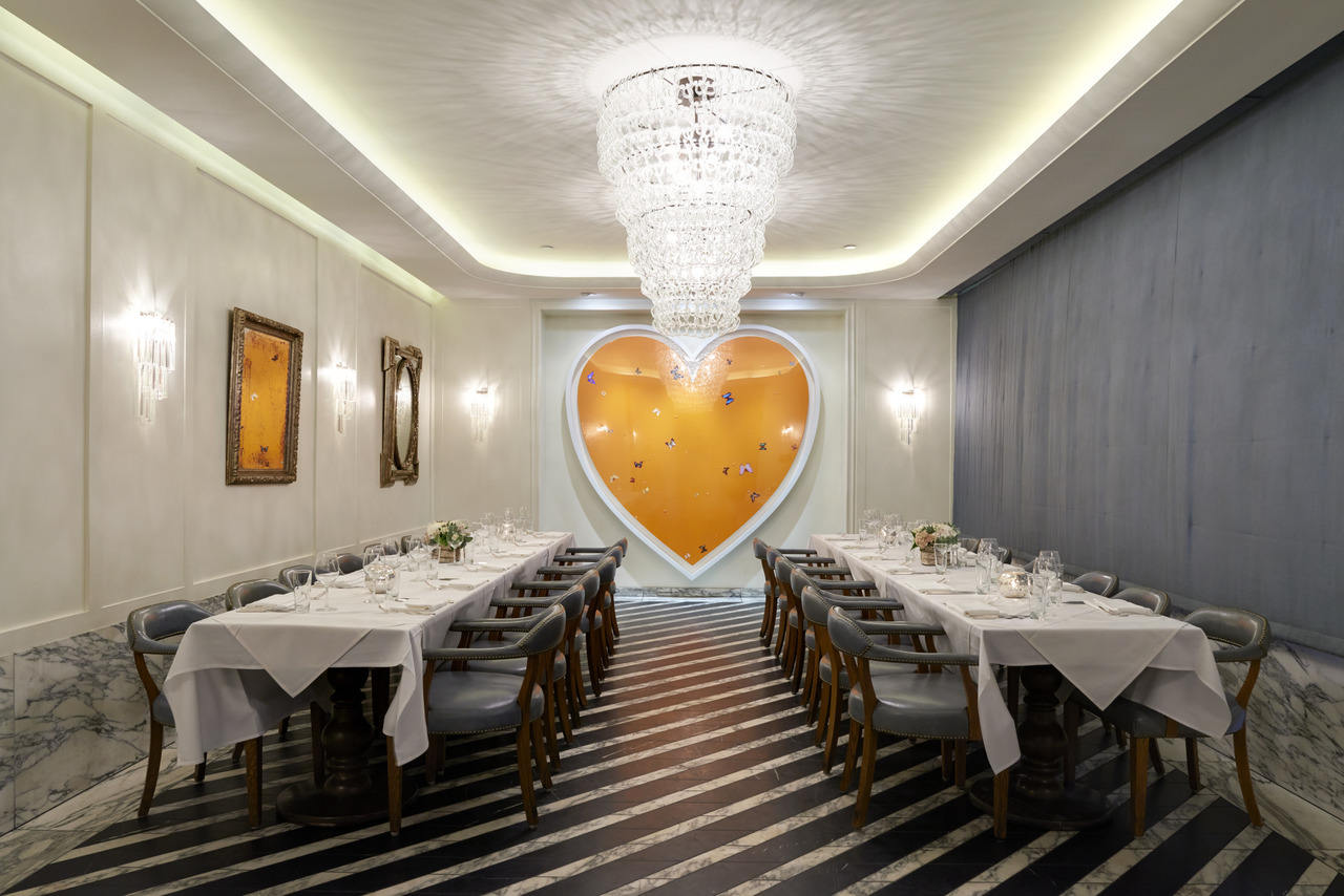Two long dining tables with a giant painting of a heart
