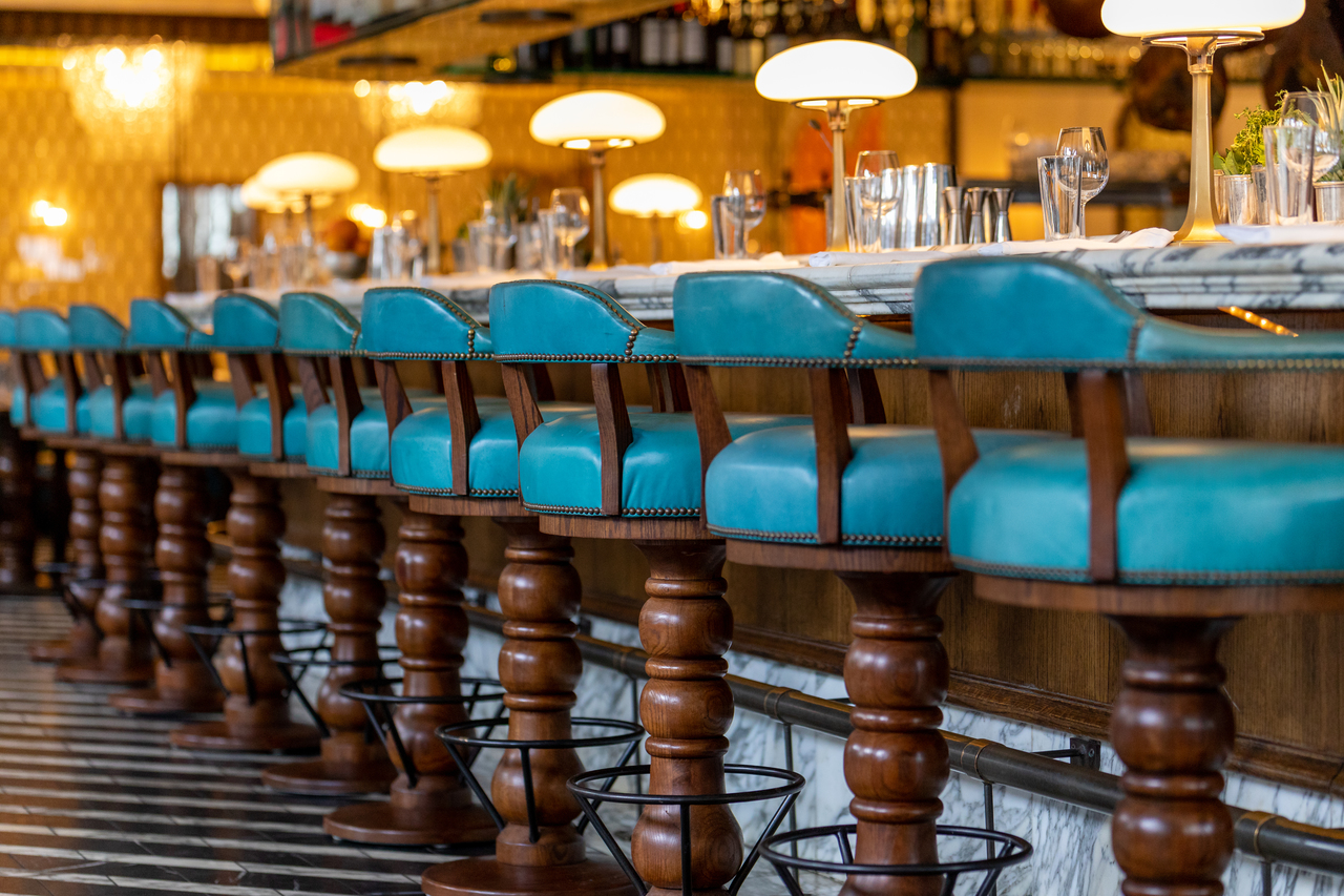 A row of blue leather bar stools